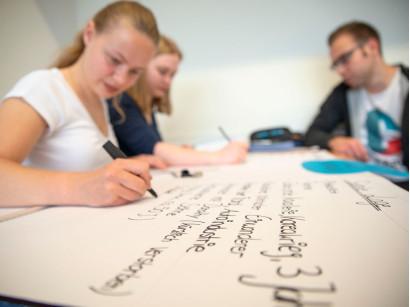 Schüler der FOSBOS Neu-Ulm gestalten eine Projekttafel.