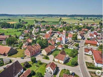 Blick auf das Gemeindebüro und die Pfarrkirche in Unterroth.