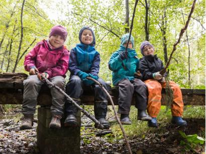 Kinder sitzen auf einem Holzsteg und angeln mit Zweigen in der Luft